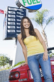Woman standing by electric car — Stock Photo