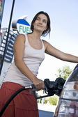 Smiling woman refueling car — Stock Photo