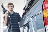 Man refueling hybrid car — Stock Photo