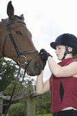 Girl tightening horse's bridle — Stock Photo