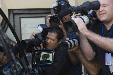 Paparazzi photographers near car