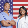 Male and female surgeons over American flag — Stock Photo #33982219