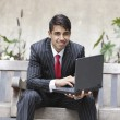 Stock Photo: Indibusinessmusing laptop