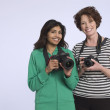 Two women holding digital cameras — Stock Photo #33983611