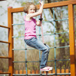 Girl climbing rope in playground — Stock Photo #33983921