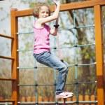 Girl climbing rope in playground — Stock Photo