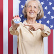 Senior woman pointing at election badge — Stock Photo