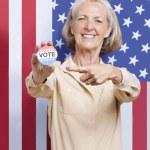 Senior woman pointing at election badge — Stock Photo