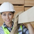 Female worker carrying plank — Stock Photo #33984057