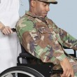Soldier in wheelchair assisted by female nurse — Stock Photo #33985899