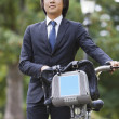 Businessman with bicycle standing at park — Stock Photo #33986397