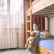 5 year old boy leans on bunk bed holding teddybear — Stock Photo #33986689