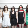 Stock Photo: Womin superhero costume with friends in police lineup