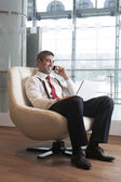 Businessman in arm chair working — Stock Photo