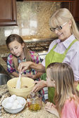 Woman with granddaughters mixing batter — Stock Photo
