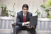 Indian businessman using laptop — Stock Photo