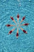Synchronised swimmers form a star — Stock Photo