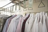 Clothes hanging in laundrette — Stock Photo