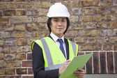 Supervisor holding clipboard at construction site — Stock Photo