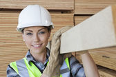 Female worker carrying plank — Stock Photo