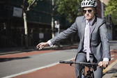 Businessman riding bicycle — Stock Photo