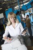 Mulher usando calculadora e verificando o jornal — Fotografia Stock