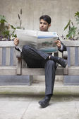 Indian businessman reading newspaper — Stock Photo