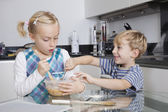 Brother and sister mixing batter — Stock Photo