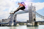 Male Athlete hurdling Tower Bridge — Stock Photo