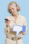 Woman with phone and fake dislike button — Stock Photo