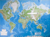 Airplane flying over world map — 图库照片