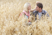 Couple relaxing amidst field — Stock Photo