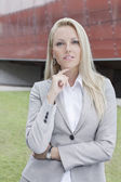 Businesswoman gesturing against office building — Photo