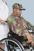 Soldier in wheelchair assisted by female nurse — Stock Photo