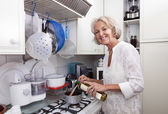 Senior woman adding olive oil to saucepan — Stock Photo