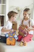 Siblings looking into each others bags — Stock Photo