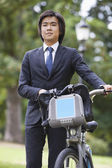 Businessman with bicycle standing at park — Stockfoto
