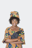 Woman in African print attire standing arms crossed — Stock Photo