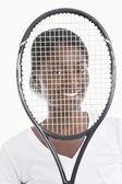Woman looking through tennis racket — Stock Photo