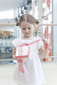 Girl unwrapping ribbon on present — Stock Photo