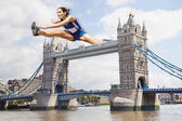 Athlete hurdling Tower Bridge — Stock Photo