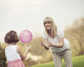 Mother throwing ball to daughter — Stock Photo