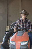 Cowboy driving utility vehicle — ストック写真