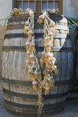 String of garlic hanging from wooden cask — Stock Photo