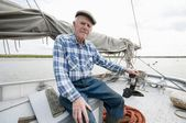 Fisherman sits on deck of boat with mast and sail — Stock Photo
