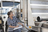 Woman inspecting timber truck — Stock Photo