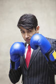 Indian businessman wearing boxing gloves — Stock Photo