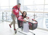 Father pushing mother, daughter in shopping trolley — Stock Photo