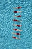 Synchronised swimmers form a ladder — Foto de Stock