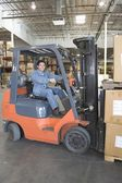 Man operating fork lift truck — Stock Photo